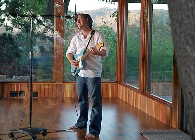 Musician recording in beautiful studio setting, mountains visible through large glass windows in background.