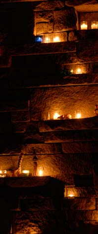 Picture of rock wall warmly lit with dozens of votive candles.